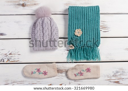 Winter handmade set of  things. Wool scarf, hat and mittens on a wooden background.  - stock photo
