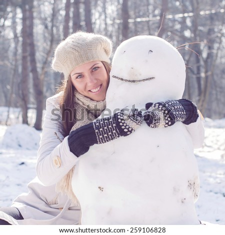 Winter Happy Woman Embracing Snowman in the park. Caucasian female wintertime outdoor. - stock photo
