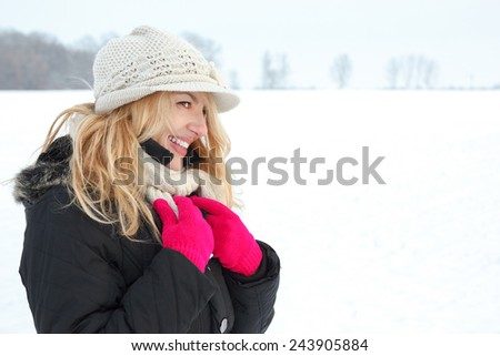 winter happy woman in snow looking aside or to someone, copy space outside on cold winter day. Portrait Caucasian smiling female model with pink gloves in first snow - stock photo