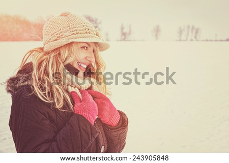 winter happy woman in snow looking aside or to someone, copy space outside on sunny cold winter vintage day. Portrait Caucasian smiling female model with pink gloves in first snow - stock photo
