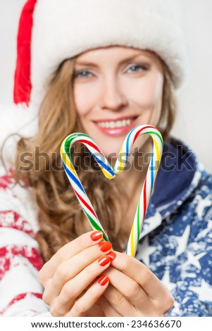 Winter heart made from candy canes holding by beautiful smiling santa woman. focus on heart and hands - stock photo