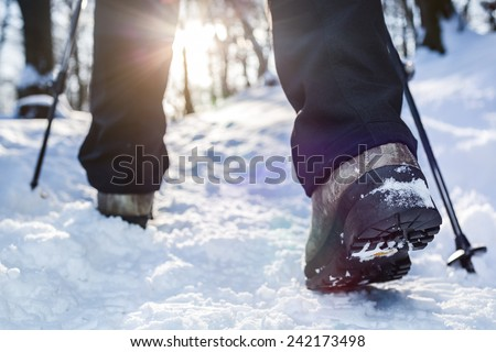 Winter hiking.  Lens flare, shallow depth of field. - stock photo