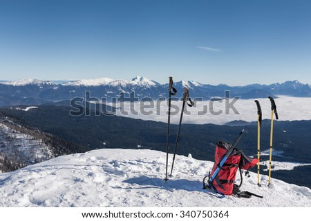 winter hiking scene; red rucksack with ice axe and two pairs of ski poles with blurred mountain ridge in the background; view towards Grintovec from Visevnik in Julian Alps, Slovenia.