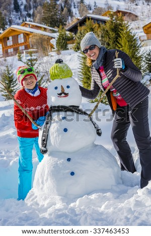Winter holiday, Christmas, happy family building snowman on ski holiday in mountains