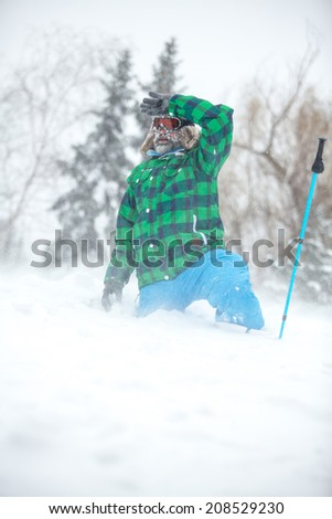 Winter holiday, travel, hiking - happy traveler enjoy winter extreme vacation in snow, snow is blowing, stormy weather - stock photo