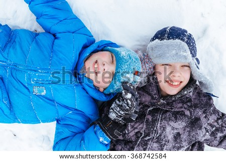 Winter holidays amusement. Two happy eleven years boys, lying on snow. - stock photo