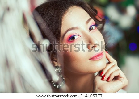 Winter holidays and Girl's best friends concept. Close up portrait of rich young asian woman smiling wearing expensive vintage diamond earrings. Perfect evening make-up. Vintage style. Indoor shot