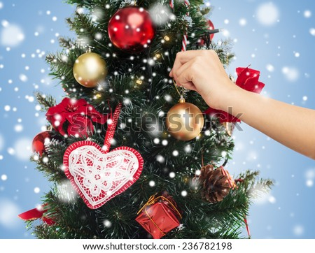 People Decorating For Christmas christmas decorating hand over tree stock images, royalty-free
