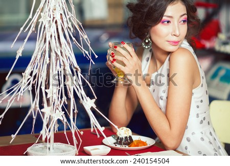 Winter holidays celebration concept. Portrait of a brunette in retro polka-dot sleeveless dress drinking tea, eating cake in restaurant.  - stock photo