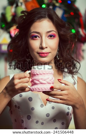 Winter holidays celebration concept. Portrait of doll like brunette in retro polka-dot sleeveless dress drinking tea or coffee in restaurant, cafe. Homemade christmas decoration. Close up. Indoor shot - stock photo