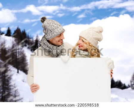 winter, holidays, christmas, advertisement and people concept - smiling couple in winter clothes with white blank billboard over snowy mountains background - stock photo