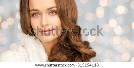 winter holidays, christmas and people concept - smiling young woman in white knitwear over shiny lights background