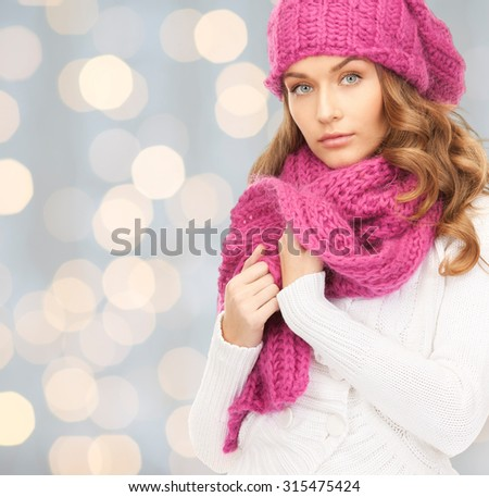 winter holidays, christmas and people concept - young woman in hat and scarf over lights background - stock photo