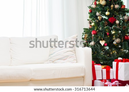 winter holidays, decoration and celebration concept - christmas tree, gift boxes and sofa at home room - stock photo