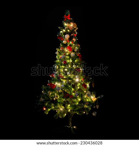 winter, holidays, decoration and illumination concept - beautiful decorated and illuminated christmas tree over black background - stock photo