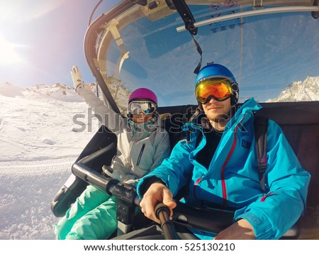winter holidays - happy couple taking selfie in chairlift at ski resort