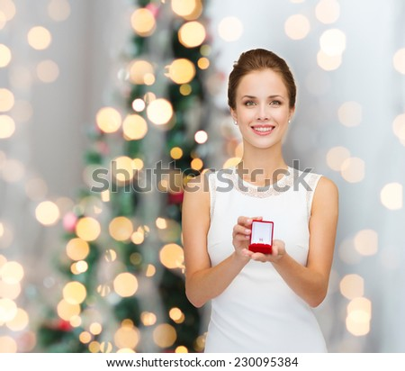 winter holidays, presents and people concept - smiling woman in white dress holding red gift box with diamond ring over christmas tree lights background - stock photo