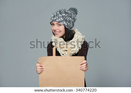 Winter holidays sale, shopping, Christmas concept. Portrait of smiling woman wearing warm winter hat and muffler showing shopping bag with empty copy space - stock photo