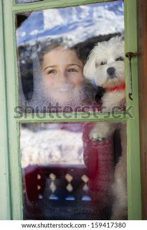 Winter holidays, ski holidays, apres ski - child with puppy  in a room apartment - stock photo
