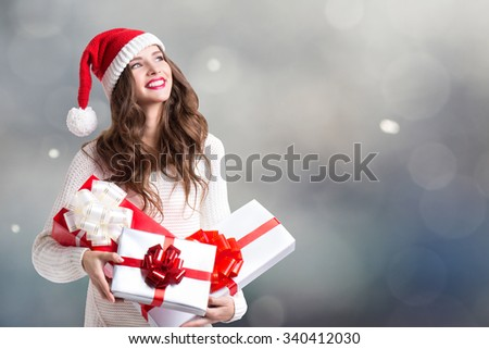 Winter holidays. Smiling young woman in santa helper hat with gifts over lights background. - stock photo