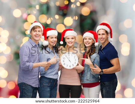 winter, holidays, time and people concept - group of smiling teenagers in santa helper hats with clock pointing finger over christmas tree lights background - stock photo