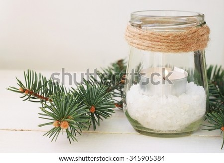Winter home relaxing time. Pretty homemade candle holder - tea light in jar with salt and green pine boughs. Rustic style table decor  - stock photo