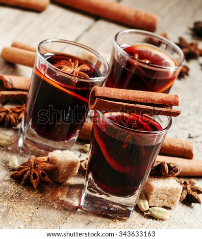 Winter hot mulled wine with cinnamon, star anise, orange and brown cane sugar in a small glass on the old wooden background, selective focus