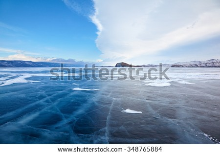 Winter ice landscape on Siberian lake Baikal with dramatic weather clouds front before the Storm - stock photo