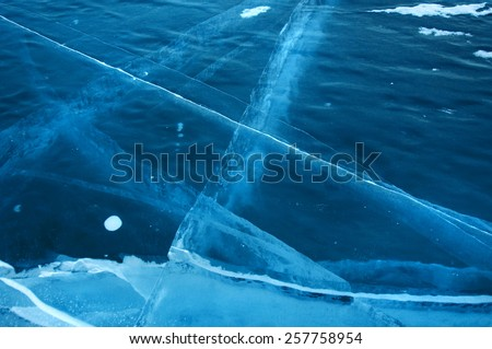 Winter. Ice on the surface of Lake Baikal. Ice thickness of about one meter. Cracks in the ice surface.  Used toning of the photo. - stock photo