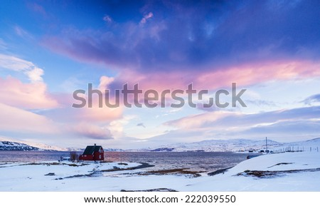 Winter in Norway - Sunset in mountains with red house and the ocean. - stock photo