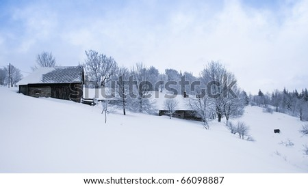 Winter in scenic mountain village covered with snow - stock photo