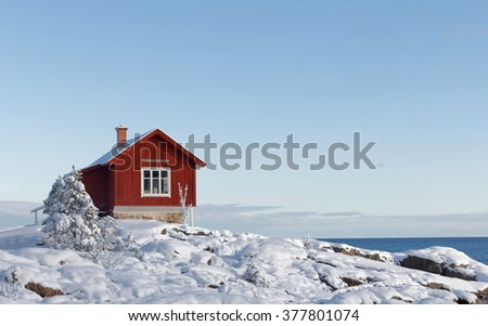 Winter in the archiplelago and a red cottage. The ground and trees covered with snow - stock photo