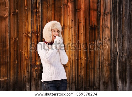 Winter in the country style. Smiling young woman in white knitted sweater and furry hat blowing warm breath on her hands in the front of rustic wood wall - stock photo