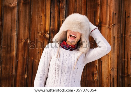 Winter in the country style. Smiling young woman in white knitted sweater pulled furry hat over her eyes in the front of rustic wood wall - stock photo