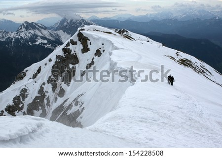 Winter in the mountains; two climbers ascending the snowy ridge of Begunjscica (2060 m).  - stock photo
