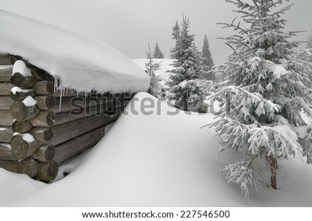 Winter in the village. Old wooden house in the snow - stock photo