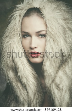 winter is coming, beautiful young woman with artificial fur hood portrait, studio shot, closeup