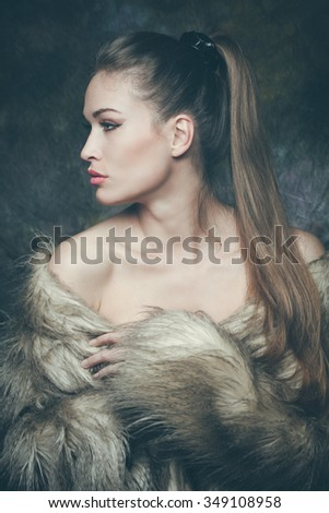 winter is coming, beautiful young woman with artificial fur  portrait, studio shot, profile - stock photo