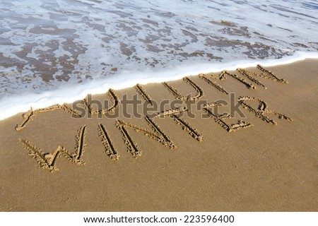 Winter is coming concept - inscription Autumn and Winter written on a sandy beach, the wave is starting to cover the word Autumn. - stock photo