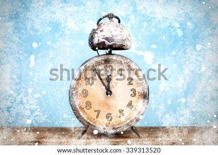 Winter is coming. Frozen retro alarm clock five minutes before twelve, midnight, covered by snow,  - stock photo