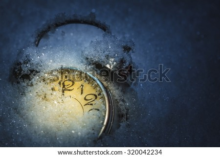 Winter is coming. Frozen retro alarm clock pointing twelve o'clock, midnight, covered by snow, dark background. Shallow depth of field. - stock photo