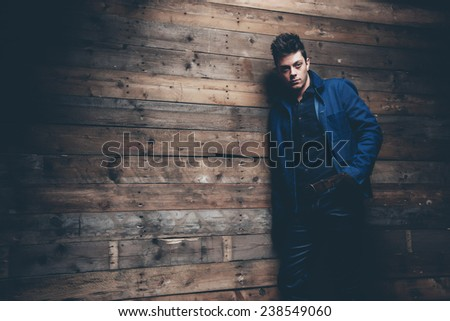 Winter jeans fashion man with short dark hair. Wearing blue jeans, jacket and brown leather gloves. Leaning against old wooden wall.