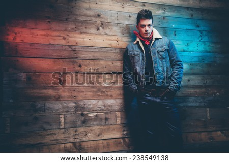 Winter jeans fashion man with short dark hair. Wearing jeans jacket and trousers. Leaning against old wooden wall. - stock photo