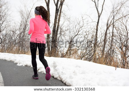 Winter jogging in park - female runner from the back exercising her cardio wearing pink jacket, active leggings and running shoes on city path. - stock photo