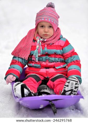 Winter joy - small kid in sledge - stock photo