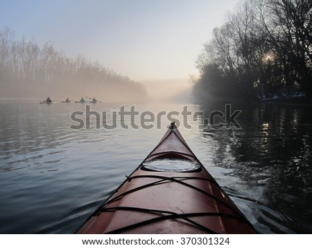 Winter kayaking in Danube river. View of red kayak on the sunset over the misty river