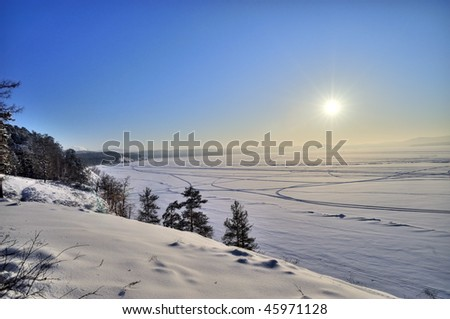 Winter lake shore with evergreen forest and sun at Urals, Russia - stock photo