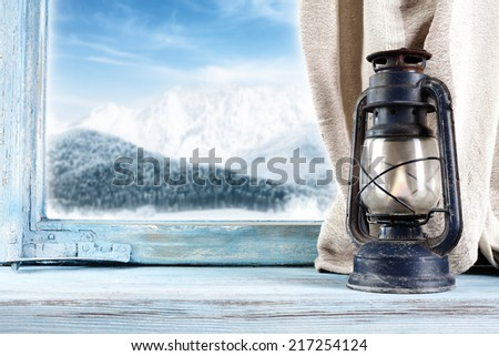 winter landscape and lamp on window  - stock photo