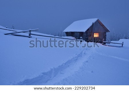 Winter landscape at night. Wooden house with a light in the window. The trail in the snow. Christmas view - stock photo