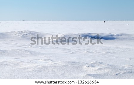Winter landscape. Deep blue sky and snow on frozen Baltic Sea with people walking on ice - stock photo